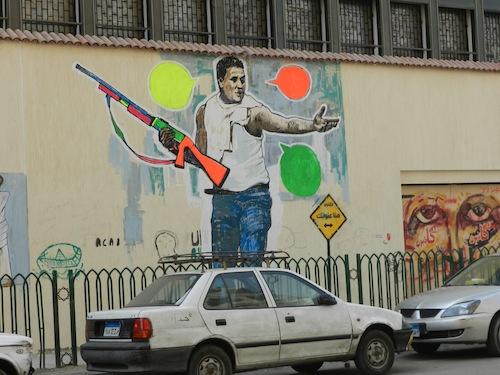 Portrait de Sambu sur le mur de la rue Mohammad Mahmoud (21 février 2012). Sambu aurait saisi une arme à feu des forces de police en tentant de défendre d'autres manifestants violemment attaqués. Il a été condamné trois ans de prison.
