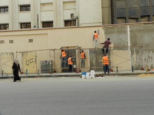 Des agents effaçant les graffitis en préparation des célébrations officielles du premier anniversaire de la révolution du 25 janvier.